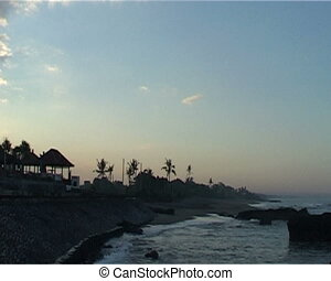 Sandy beach of Bali in the evening with few cabins and palms...