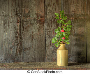 Still life image of dried flowers in rustic vase against weathered wooden background