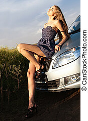 sexy young beautiful girl in a short dress lying on the hood...
