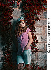 lonely girl in a hat stands next to the with wild grapes at night in the darkness alley