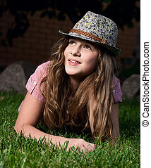 little smiling girl lying on the grass in the garden at night