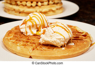 Belgian waffles with ice-cream and syrup on white plate