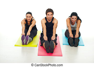 Cheerful group of fitness people stretching their bodies and...