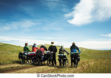 Group of bicyclists going on road Lake Baikal island Olkhon