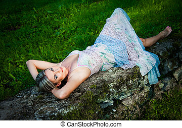 Portrait of attractive woman in blue sundress lying on...