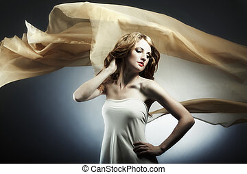 Portrait of the young woman against a flying fabric