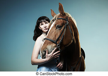 Beautiful young woman with a brown horse