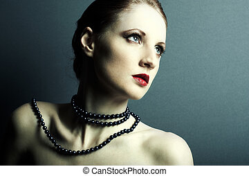 The beautiful young girl with a dark blue beads on a neck