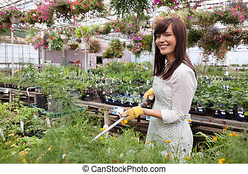 Female Worker Water Plants - Female worker water plants with...