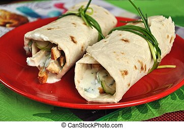 Two shawarmas on red plate