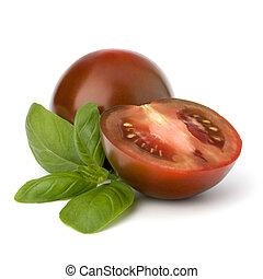 Tomato kumato and basil leaf isolated on white background