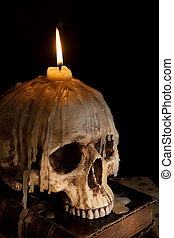 Candle on skull 5 - Halloween image with a burning candle on...