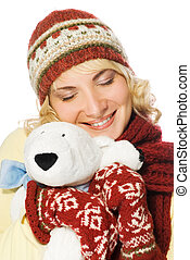 Beautiful girl in winter clothing with a polar bear toy