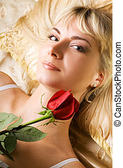 Young beautiful woman with red rose