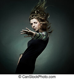 Fashion portrait of the beautiful woman with flying hair