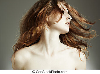 Portrait of the beautiful woman with red curly hair