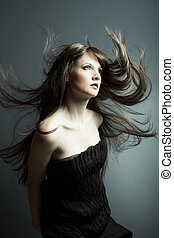 The young beautiful girl in black dress with developing hair