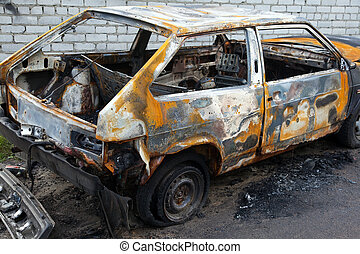 Burnt cars at the front of a brick wall