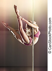 Young pole dance woman. On wall background.