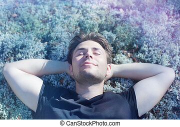 Young man resting on grass in forest