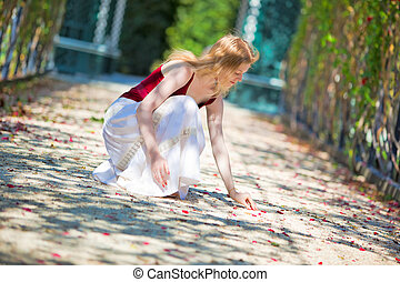 Young woman picking up petals