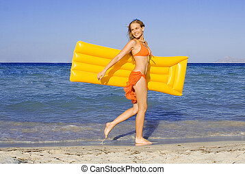 happy young woman walking on beach with airbed on summer vacation