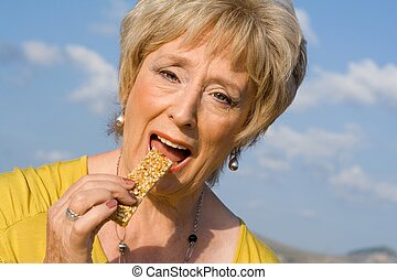 happy senior woman eating healthy cereal bar