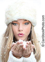 beautiful girl blowing christmas or new year wishes