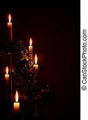 lit christmas holiday candles with holly