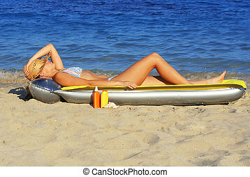woman laying on lilo airbed on beach sunbathing with tanning...