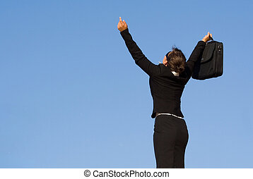 young business woman arms raised in triumph happiness and success