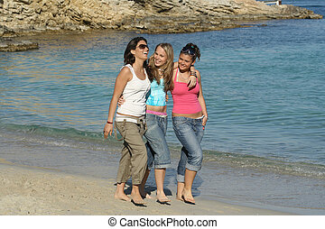 group of girls walking along the beach on summer holiday