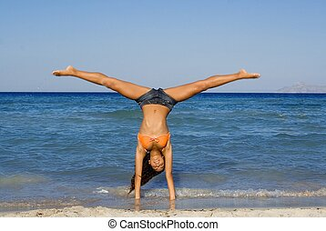 happy woman doing cartwheel or handstand on summer beach holiday in mallorca