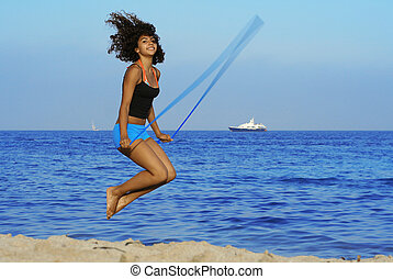 healthy woman skipping on beach on summer vacation