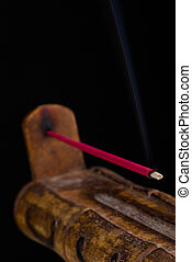 Incense stick - A burning incense stick on a handcrafted...