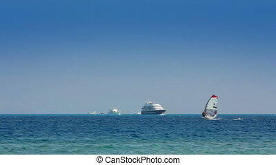 yachts and surfers on turquoise sea