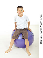 Boy sitting on pilates ball - Smiling boy sitting on pilates...
