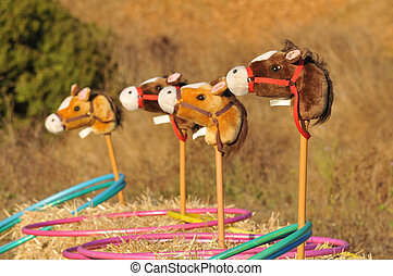 Four toy horse head wait for ring toss game. - Fuzzy horse...