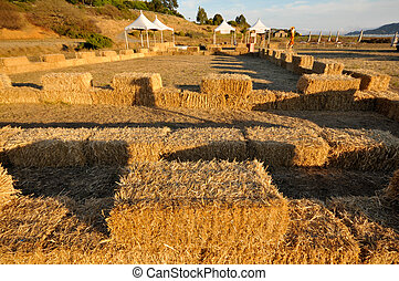 Bails of hay surround a field at faire - Tents next to a...