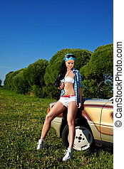 young sexy woman stay near retro car at summer sunset