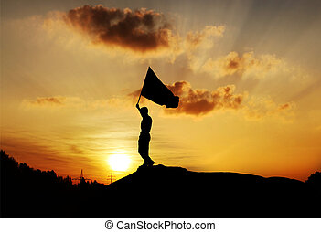 Man holding Flag in Sunset
