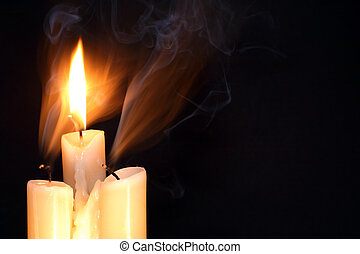 Three Candles - One burning candle between two just...