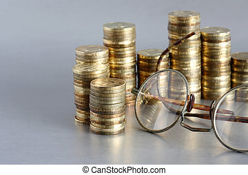 Vintage Bookkeeping - Closeup of coins and old spectacles on...