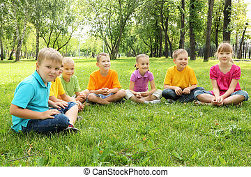 Group of children sitting together in the park