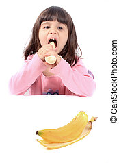 Little girl eating banana - Young little girl making a funny...