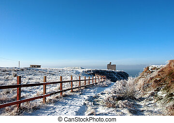 fenced walk to ballybunion castle in winter snow - snow...