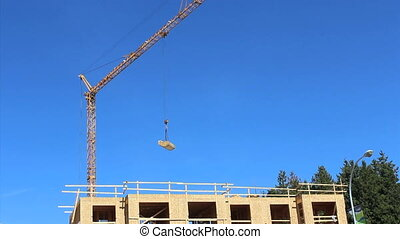Constuction Crane Carrying Lumber