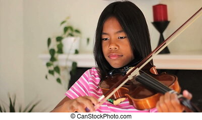 Asian Girl Practicing Violin - A pretty 9 year old Asian...