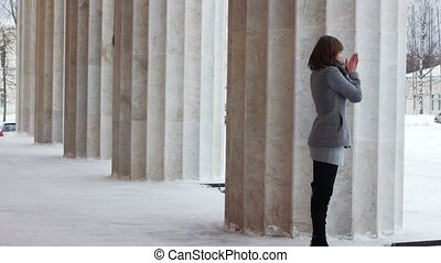 Young female model posing near column