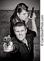 Gunfight - Young man and woman with guns in a stairwell